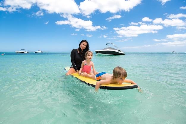 Близнецы, мальчик и девочка с мамой, занимаясь серфингом в океане на доске