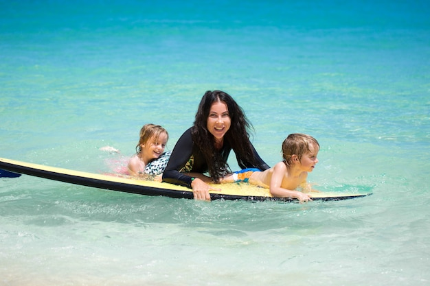 Twins, boy and girl with mom surfing in the ocean on a blackboard