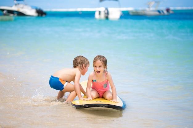 Близнецы брат и сестра повеселиться с серфингом в океане