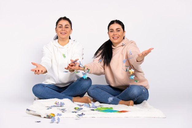 Twins on the floor sitting on a soft blanket smile and throw the puzzle into the camera white