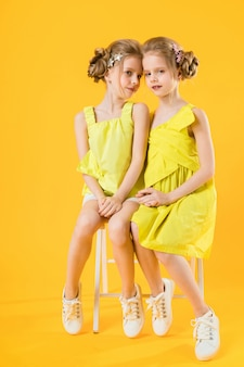 Twins girls are sitting on chair on yellow