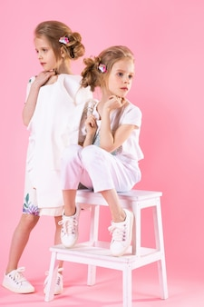 Twins girls in bright clothes posing near the stairs with two steps on a pink