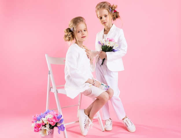 Twins girls in light clothes with bouquets of flowers posing near a chair on pink