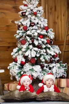 새해 의상을 입은 쌍둥이, 침대에 누워 미소 짓고 기쁨