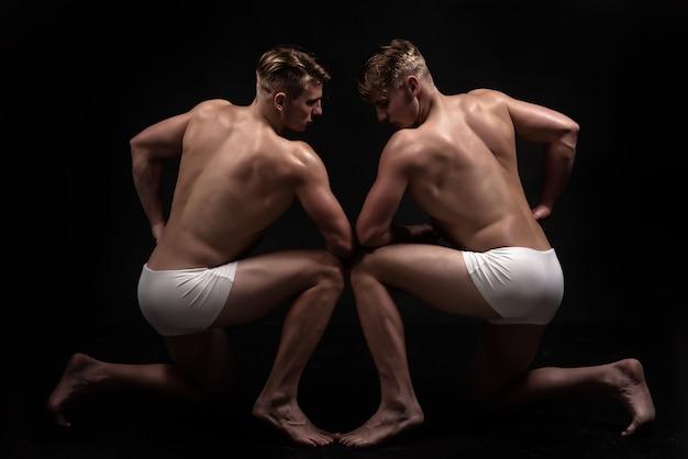 Близнецы мужчины с мускулистым телом в позе.