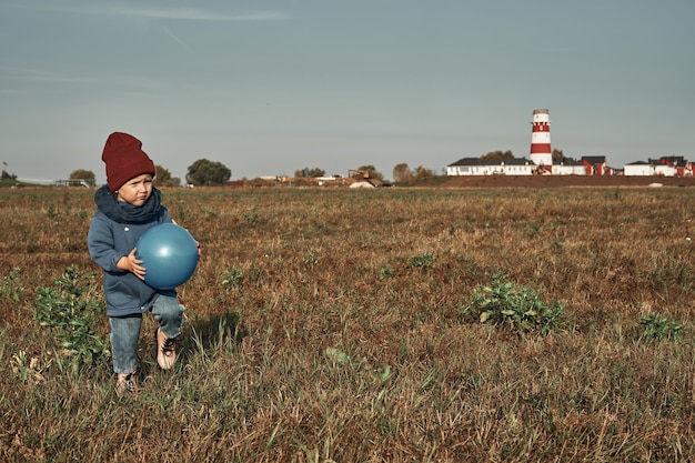 Twins play ball in the field, a lighthouse in the background, children two years old. autumn walks in nature.