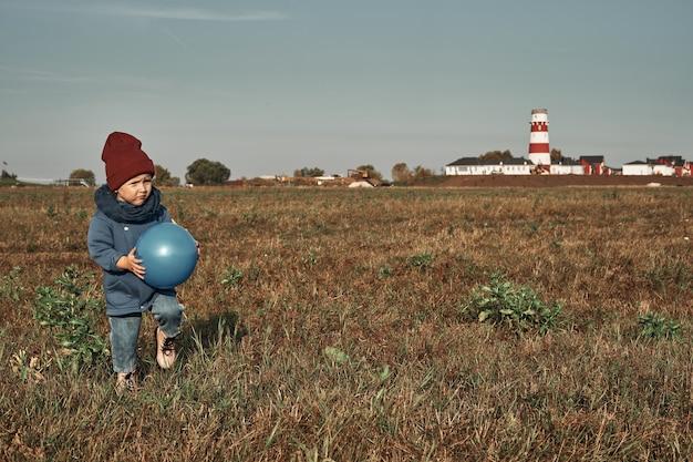 쌍둥이는 들판에서 공을 치고, 배경에는 등대, 2 살짜리 아이들이 있습니다. 가을은 자연 속에서 걷는다.