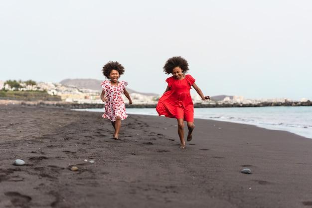 Близнецы сестры бегут по пляжу вместе