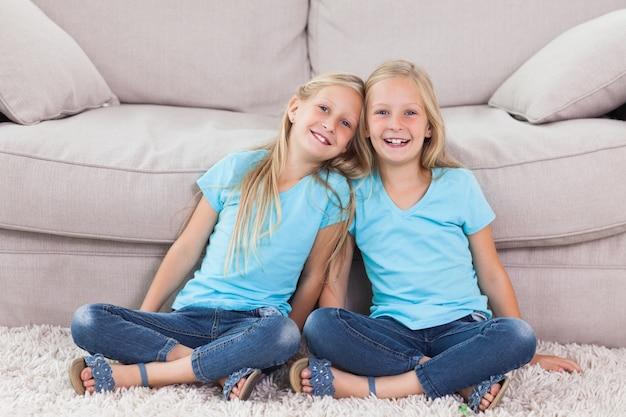 Twins sitting on a carpet