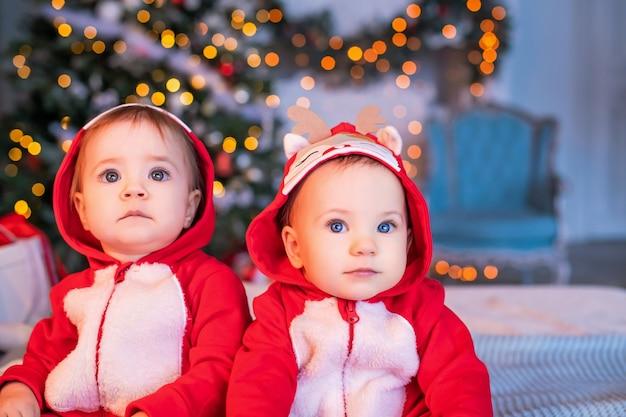 赤いサンタのトナカイのスーツを着た双子の幼児は、クリスマスツリーを背景に自宅で隣同士に座っています