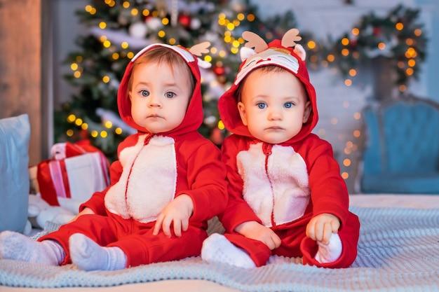 빨간 산타의 순록 양복을 입은 쌍둥이 유아는 크리스마스 트리를 배경으로 집에서 서로 옆에 앉아 있다