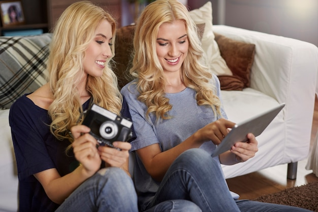 Twins with retro camera and modern tablet