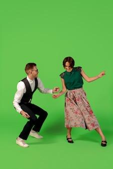 트위스트. 녹색 스튜디오 배경에서 격리된 춤을 추는 구식 젊은 여성. 아티스트 패션, 모션 및 액션 컨셉, 청소년 문화, 패션 복귀. 세련 된 젊은 남자와 여자.