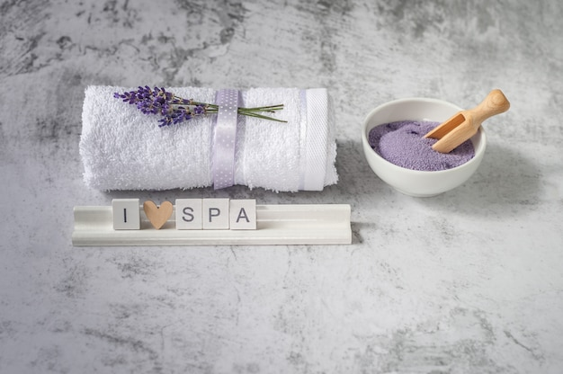 Twisted bath towel with bath salt and wooden letters spelling i love spa.