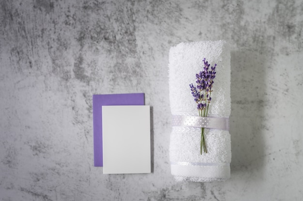 Twisted bath towel with lavender and blank card on light gray. spa concept.