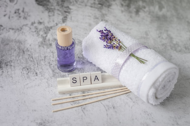 Twisted bath towel with lavender and wooden letters spelling