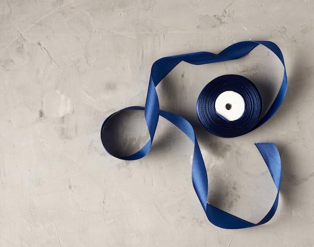 Twisted blue silk ribbon on concrete