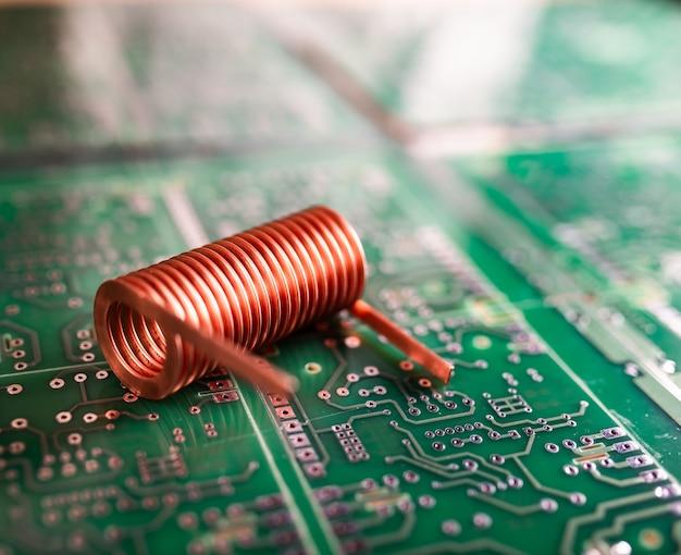 꼬인 구리선은 녹색 칩에 있습니다. 컴퓨터 하드웨어 개념. 노트북 컴퓨터 및 디지털 기술 생산 공장