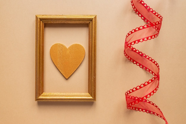 Twisted decorative ribbon and golden photo frame with wooden heart.