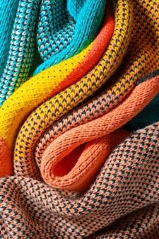 구조와 질감이 다른 겨울 옷의 화려한 니트 직물의 꼬인 주름. 부드러운 모양 배경. 부드럽게 접힌 멀티 컬러 니트 원단