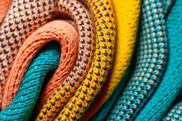 구조와 질감이 다른 겨울 옷의 화려한 니트 직물의 꼬인 주름.