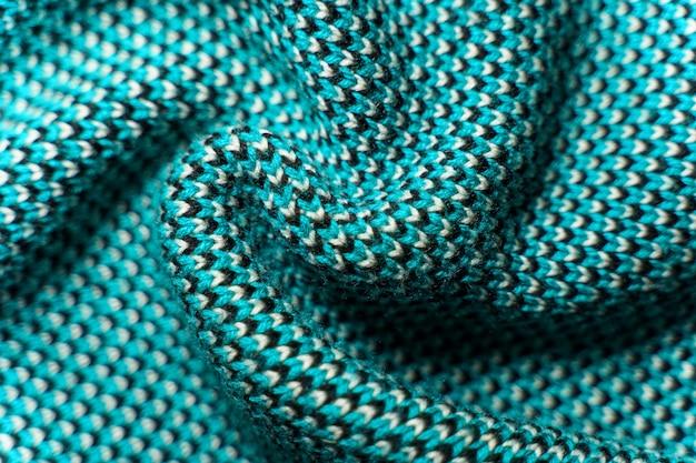 青、黒、白の糸のパターン要素を持つ合成ニット生地のねじれた折り目がクローズアップします。マルチカラー柄のニット生地の風合い。バックグラウンド