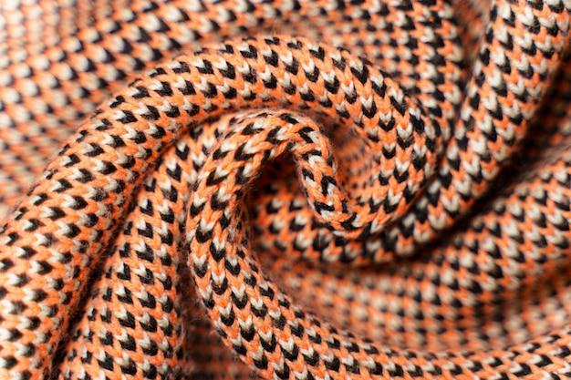 赤、黒、白の糸のパターン要素を持つ合成ニット生地のねじれた折り目がクローズアップします。マルチカラー柄のニット生地の風合い。バックグラウンド