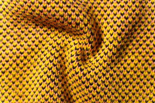 Twisted folds of synthetic knitted fabric with pattern elements of yellow, black and white yarns close up.