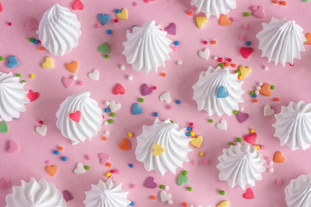 Twisted meringues with confectionary decorations on pink background.