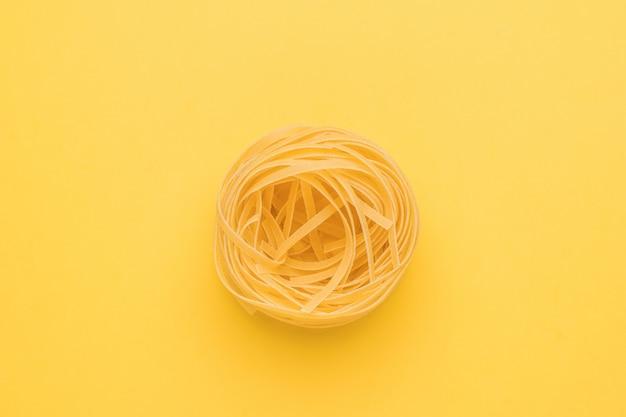 明るい黄色の背景にツイストパスタ。デュラム小麦で作られた製品。
