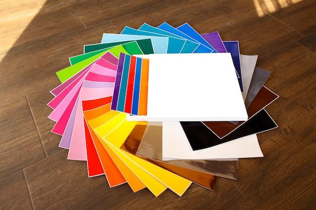 흰색 배경 위에 분리된 다채로운 12x12 접착 용지의 뒤틀린 더미. 모듬된 색상입니다.