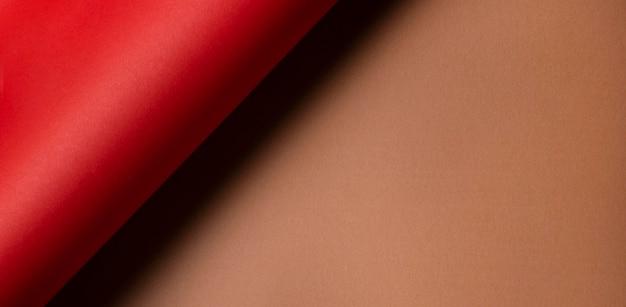 ツイストした赤い紙とコピースペースの茶色の紙