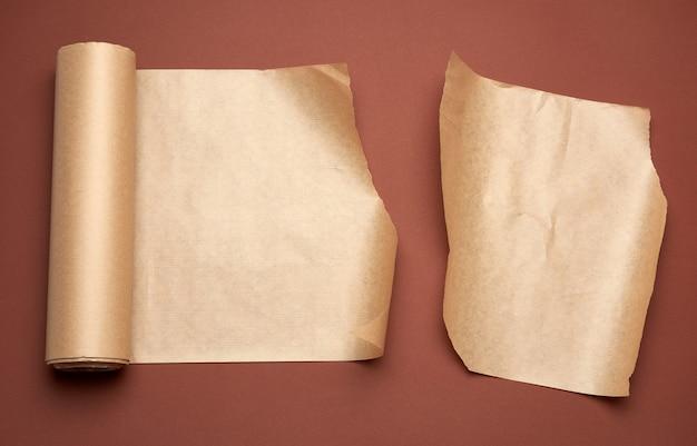 Витой рулон коричневой пергаментной бумаги на коричневом фоне