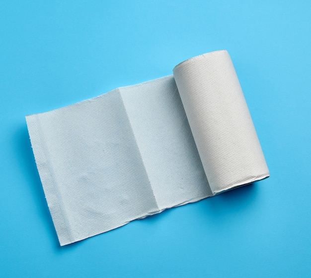Twisted roll of white paper towel on a blue . paper sheet