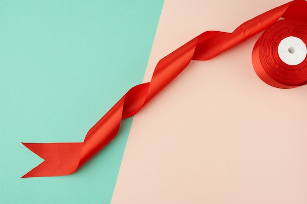 Twisted silk red ribbon on a green-beige background, top view, cropped end