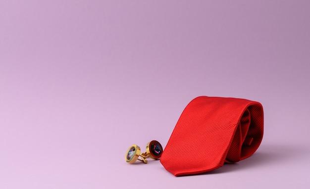 紫の背景にツイストシルクの赤いネクタイとカフスボタン、クローズアップ