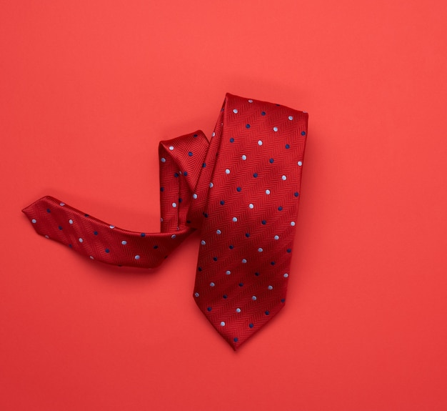 Twisted silk red tie on red background
