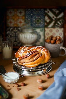 Twisted sweet bread canelbulle or cinnamon roll with chocolate and nuts on rustic background