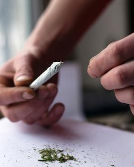 Скручивание косяка, курение конопли сорняков крупным планом.