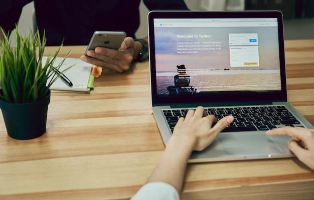 女性はラップトップを使用してオープンtwitterアプリケーション
