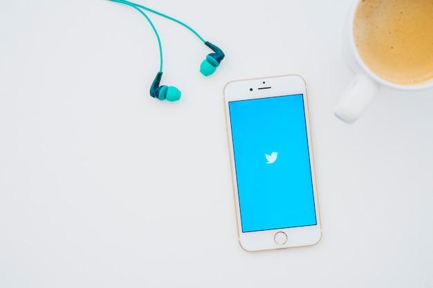 イヤホン、コーヒーマグ、twitterアプリ付き携帯電話