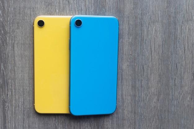 Два 2 новых сотовых мобильных смартфона, телефоны синего и желтого цвета на деревянном сером цвете. плоская планировка, натюрморт, набор современных красочных гаджетов, приспособлений. флаг украины.