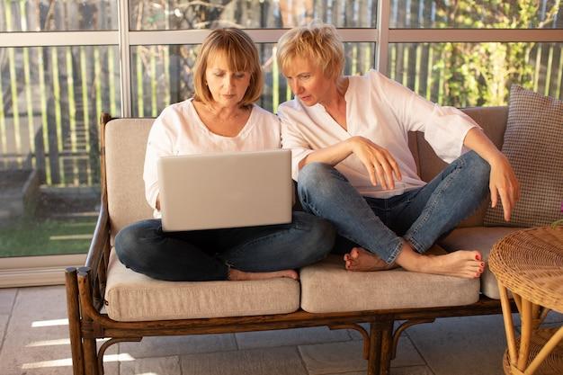 평상복 차림의 2명의 55세 여성이 업무와 커뮤니케이션을 위해 노트북을 사용합니다