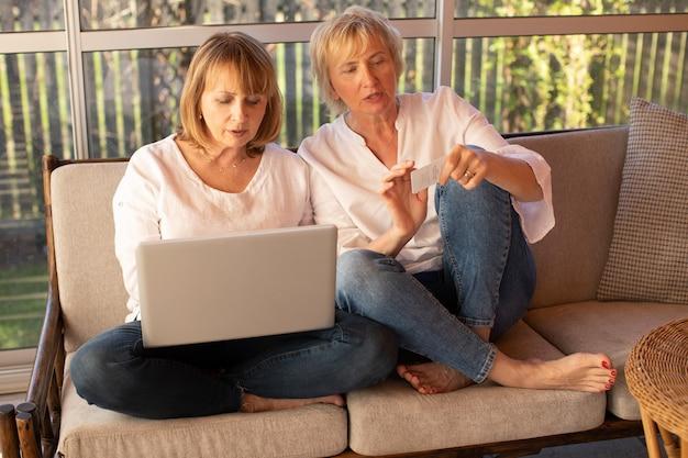 캐주얼 옷을 입은 2명의 55세 여성이 온라인 쇼핑을 위해 노트북을 사용합니다.