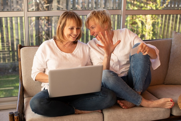 평상복 차림의 2명의 55세 여성이 집에서 노트북을 사용하여 온라인 쇼핑을 합니다.