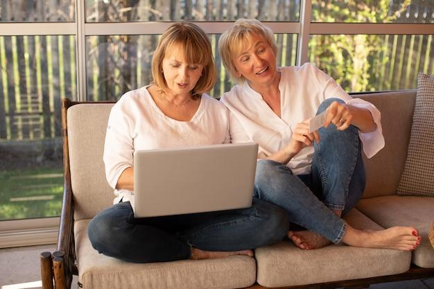 カジュアルな服装の55歳の女性2人が、自宅のソファに快適に座ってノートパソコンを使用してオンラインで買い物をしています