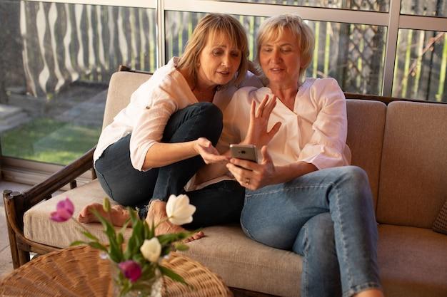 Две 55-летние женщины используют смартфоны для чтения социальных сетей, фото образа жизни