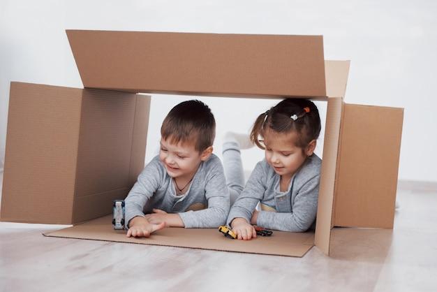 2人の小さな子供男の子と女の子がちょうど新しい家に引っ越しました。コンセプト写真。子供たちは楽しんで、小さな車で遊んでいます