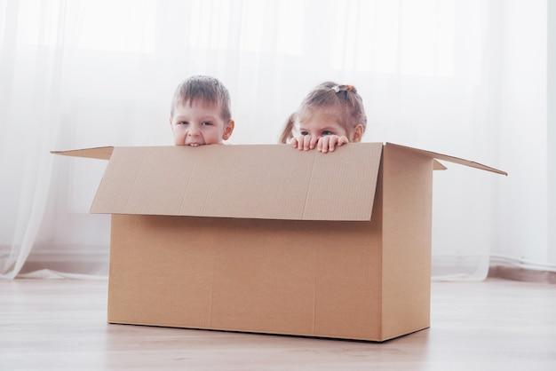Двое маленьких детей, мальчик и девочка, только что переехали в новый дом. концептуальное фото .. дети веселятся.