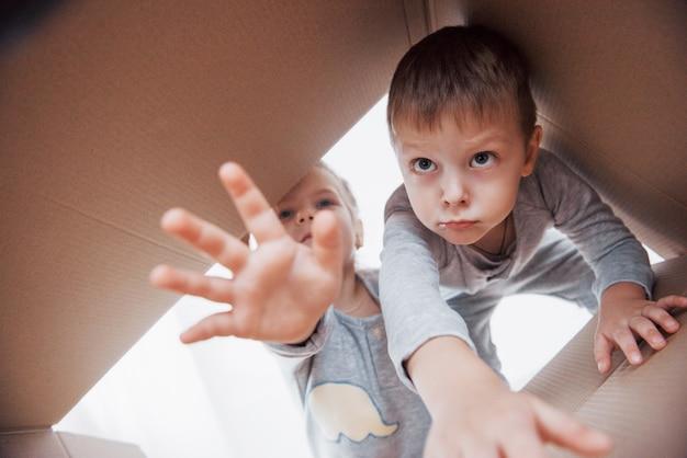 段ボール箱を開けてその真ん中に登る2人の小さな子供男の子と女の子。子供たちは楽しんでいます。